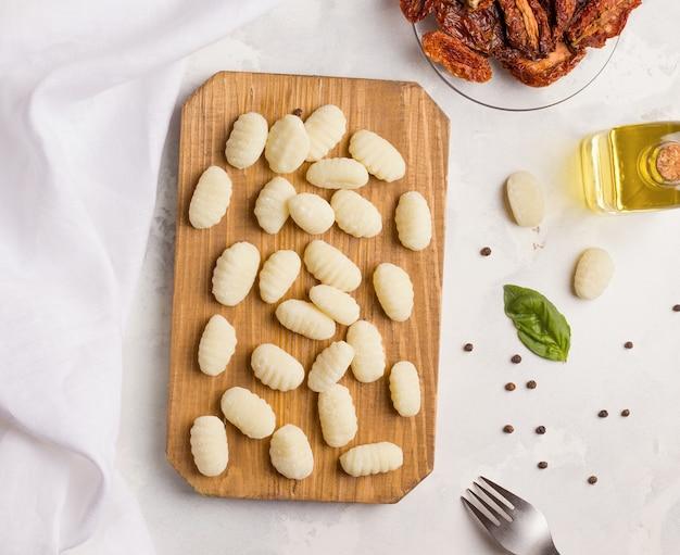 スパイスとハーブの横にある木の板にニョッキポテトのイタリア料理。上から見る