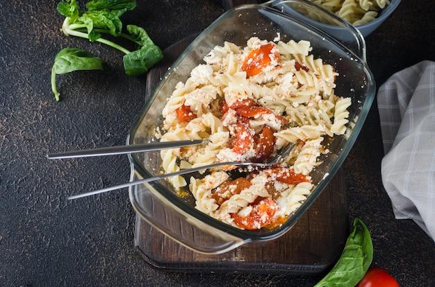 暗い背景に焼きたてのフェタチーズとトマトを混ぜたパスタのイタリア料理。フェタパスタ。トレンドのバイラルレシピ、フラットレイ、コピースペース