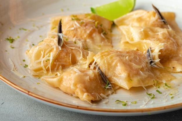 접시에 파마산 치즈를 곁들인 이탈리아 요리 라비올리