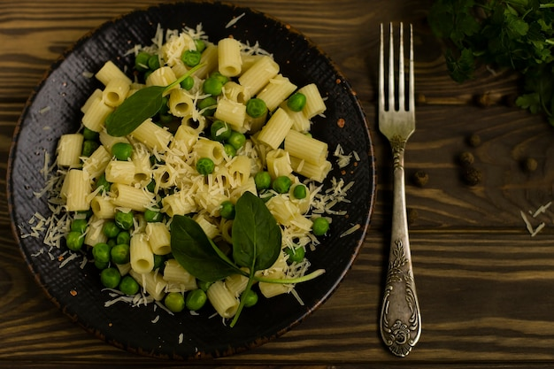 木製の背景に、ハーブとチーズのイタリアのディタリーニパスタ。