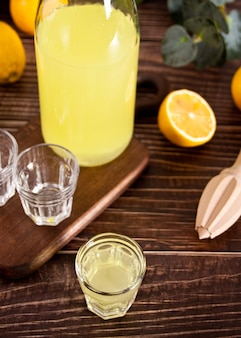 Italian drink lemon liqueur limoncello in a bottle and empty glasses on the wooden table.