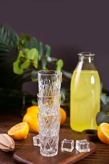 Italian drink lemon liqueur limoncello in a bottle and empty glasses