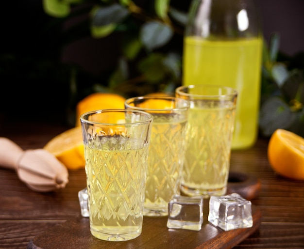 Italian drink lemon liqueur limoncello in glasses on the wooden table.