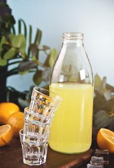 イタリアの飲み物レモンリキュールリモンチェッロボトルと木製のテーブルの上の空のグラス。