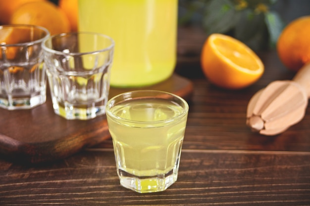 イタリアの飲み物レモンリキュールリモンチェッログラスの木製テーブル。