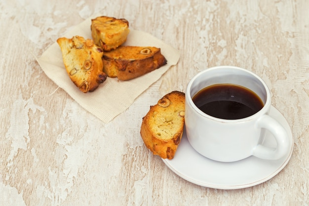 Italian dry biscuits biscotti with cup of coffee or black tea on wood table.