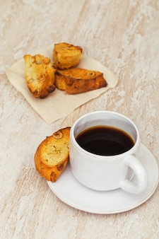 Italian dry homemade cookies cantucci on table and coffee in white cup.