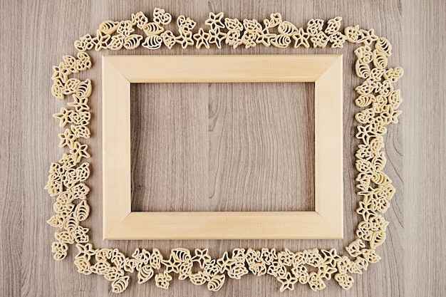 Italian dry sea pasta on beige brown wooden board with empty copyspace as decorative frame background