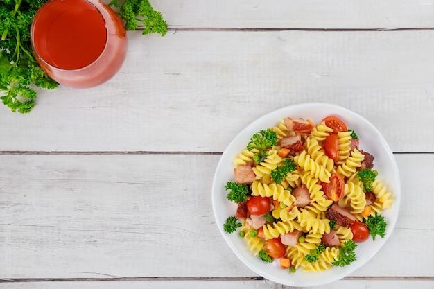토마토 주스를 곁들인 이탈리아 듀럼 밀 파스타 로티니. 건강한 식사.