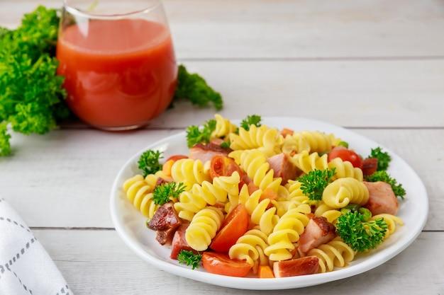 イタリアのデュラム小麦パスタロティーニとトマトジュース。健康食。