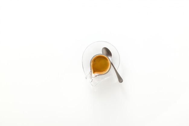 白い背景で隔離のガラスのコップにイタリアのエスプレッソコーヒー。