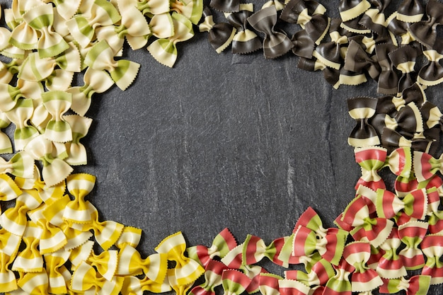 Italian farfalle pasta of different colors, the color of the flag on dark stone background, frame border.