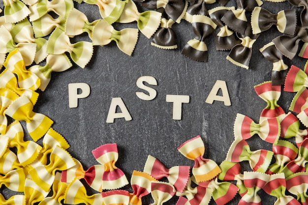 Italian farfalle pasta of different colors, the color of the flag, on dark stone background.