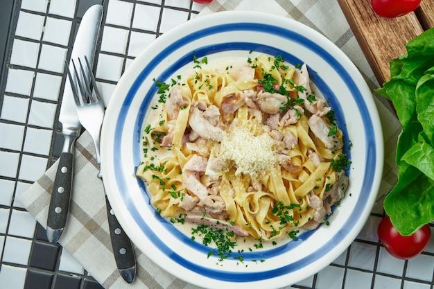 パルメザンチーズ、鶏肉、ハム、白い表面に白いセラミックボウルにハーブのチーズソースのイタリアのフェットチーネパスタ。