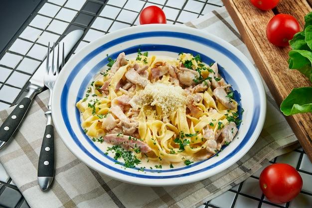パルメザンチーズ、鶏肉、ハムのチーズソースのイタリアのフェットチーネパスタ、白いテーブルに白いセラミックボウルにハーブ。おいしい食べ物のテーブル