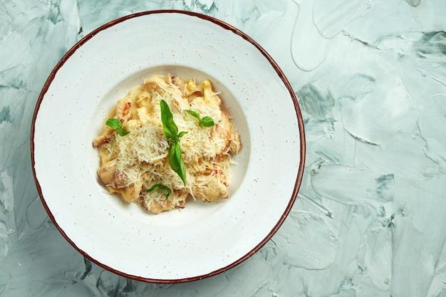 白いプレートにチキン、ベーコン、チーズのイタリアのフェットチーニパスタ