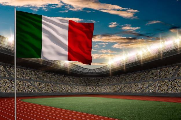 Bandiera italiana davanti a uno stadio di atletica leggera con i tifosi.