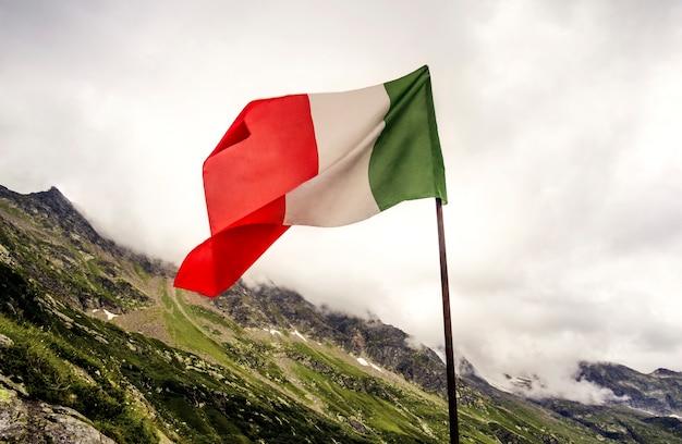 Итальянский флаг на фоне пасмурных альп
