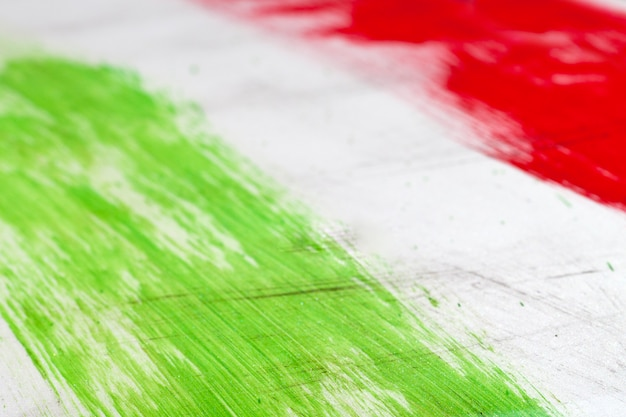 Italian flag painted with  brush strokes on white background.