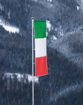 Итальянский флаг развевается ветром на полюсе на горнолыжном курорте