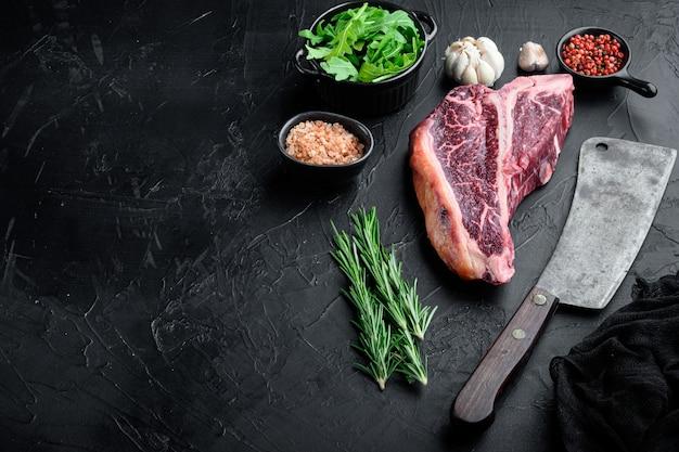 Итальянский флорентийский стейк из говядины на косточке с набором трав, на черном каменном фоне, с местом для текста