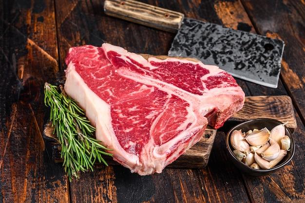 Italian florentine tbone beef meat steak with herbs on a wooden cutting board.