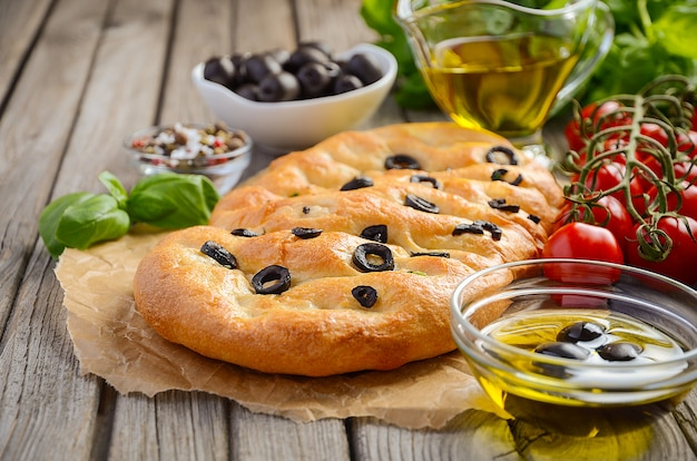 Italian focaccia bread with olives and rosemary on rustic wooden background.