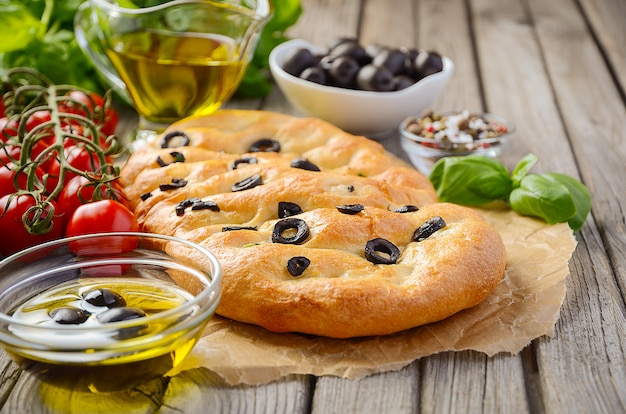 Italian focaccia bread with olives and rosemary on rustic wooden table.