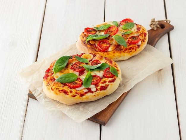 イタリアのフォカッチャまたはモッツァレラチーズ、トマト、バジルのピザ。