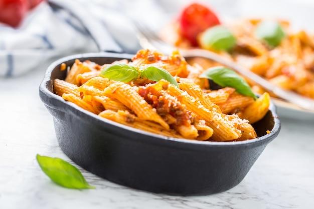 냄비에 볼로네제 소스를 곁들인 이탈리아 음식과 파스타 펜네.