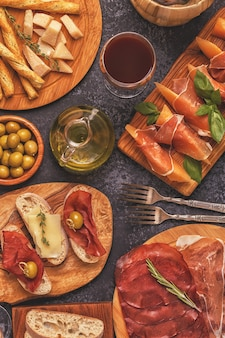 Italian food background with ham, cheese, olives, bread and wine