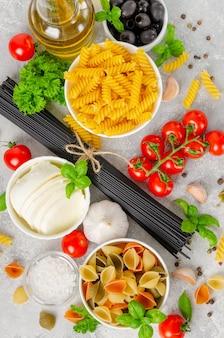 Фон итальянской кухни с сырыми макаронами, свежими помидорами, базиликом, черными спагетти, оливками, моцареллой, оливковым маслом, чесноком и петрушкой.