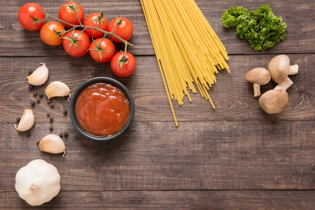 Italian food background, with tomato, garlic, pepper, mushrooms and spaghetti on wooden background