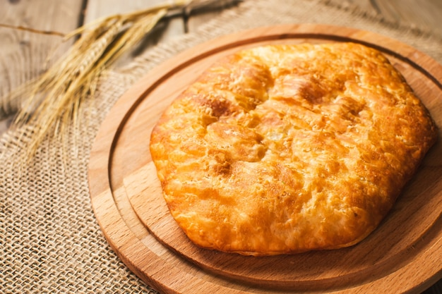 イタリア料理、ほうれん草とチーズ、木製の背景と閉じたピザカルゾーネ。焼きたて