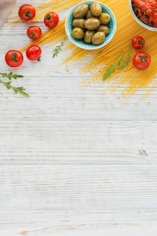 イタリア料理のコンセプト。パスタスパゲッティの準備のための成分-トマト、オリーブオイル、スパイス、ハーブ、グリーンオリーブ、トマトソース、白い木製の背景。テキスト用のコピースペースを備えたフラットレイ