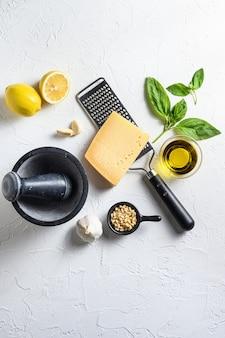 Итальянские пищевые ингредиенты для приготовления пищи на белом каменном фоне с сыром пармезан, листьями базилика, кедровыми орехами, оливковым маслом, чесноком, солью и перцем. вид сверху сверху.