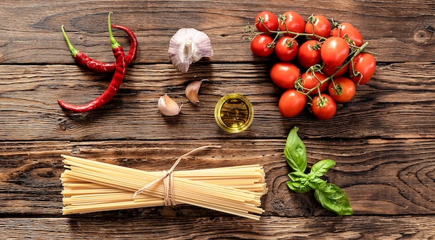 Italian food cooking ingredients with raw spaghetti on rustic wooden board top view