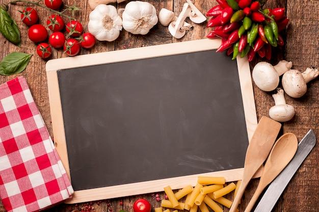 イタリア料理。石のキッチンテーブルのレシピにトマト、バジル、パスタ、黒板。コピースペースのある上面図