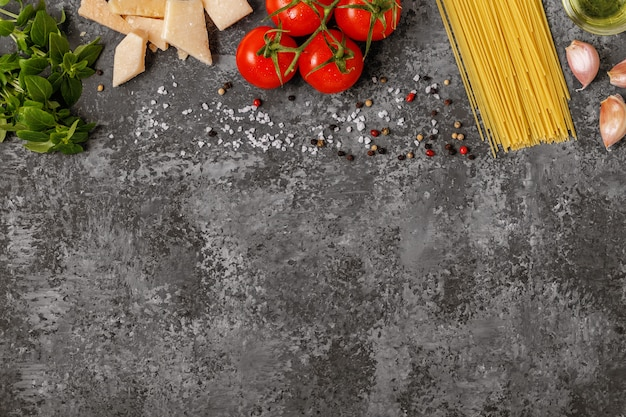Italian food cooking-tomatoes, basil, pasta, olive oil and cheese.