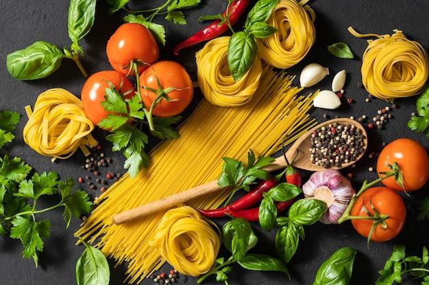 Итальянская кухня и ингредиенты. спагетти и тальятелле с помидорами, перцем, чесноком и петрушкой на темном фоне, вид сверху