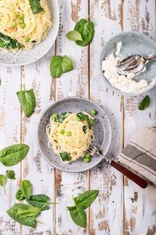 イタリア料理:新鮮な自家製タリアテッレベジタリアンエッグパスタカルボナーラ、白い木製の背景にリコッタチーズとほうれん草を添えて