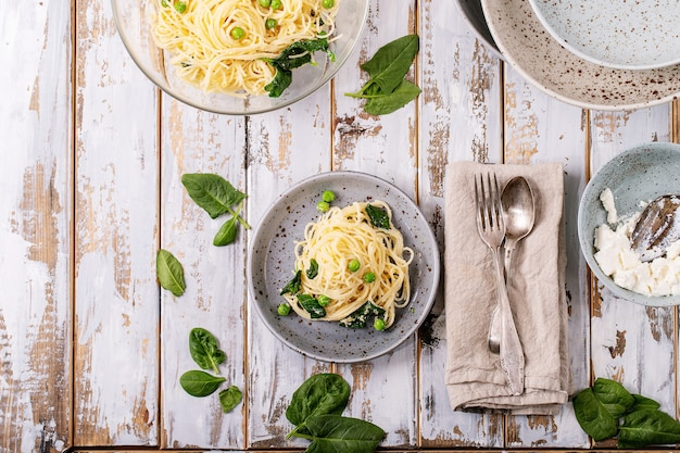 Итальянская кухня: свежая домашняя вегетарианская яичная паста тальятелле карбонара подается с сыром рикотта и шпинатом на белом деревянном фоне.