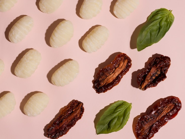 イタリア料理。ニョッキは、ピンクの背景にトマトとバジルを使った伝統的なベジタリアン料理です。パターン。上から見る