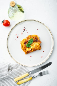 イタリア料理。ホットおいしい焼きたてのラザニアセット、プレート、白い石のテーブル、上面図、フラットレイ