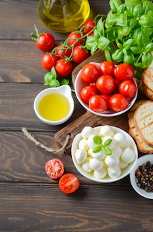 Italian food ingredients on dark wooden table.