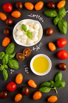 Italian food ingredients – mozzarella, tomatoes, basil and olive oil on black