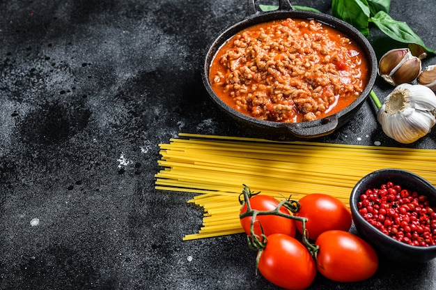Italian food ingredients for spaghetti bolognese. raw pasta, basil, ground beef, tomatoes. black background. top view. copy space