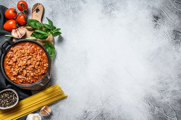 Italian food ingredients for spaghetti bolognese. raw pasta, basil, ground beef, tomatoes. gray background. top view. copy space