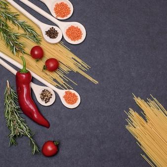 Итальянские пищевые ингредиенты. натюрморт приготовления макарон на черном фоне вид сверху. деревянные ложки со специями. рамка продуктов и овощей.