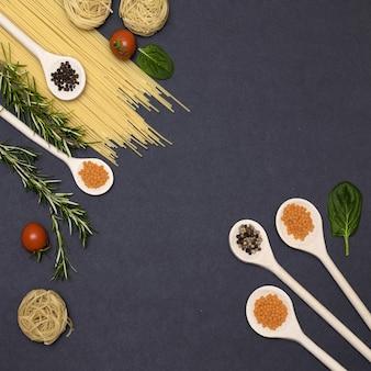 Итальянские пищевые ингредиенты. натюрморт приготовления макарон на черном фоне вид сверху. деревянные ложки со специями.
